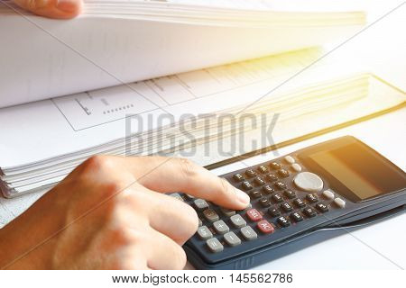 Financial data analyzing. savings finances economy. Close-up photo of a businessman's hand counting on calculator in office or home. Soft focus