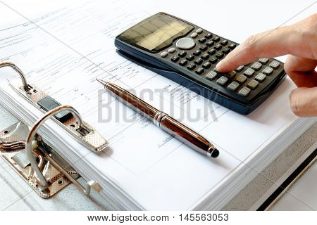 close up of man with calculator counting making notes pen on the file folder data analysis.