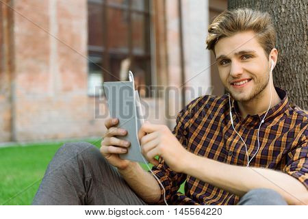 Happy young man is relaxing outdoors. He is holding tablet and smiling. Man is sitting and leaning on tree