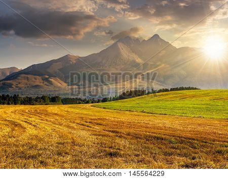Tatra mountains in evening haze behind the forest and rural field in evening light