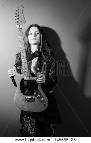 Photo of a sexy brunette woman standing and holding an electric guitar.
