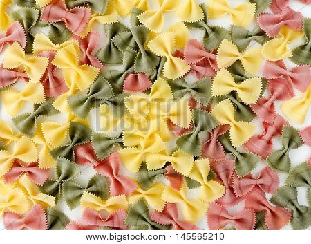 Extra large multicolored farfalle pasta spread out on a white background.