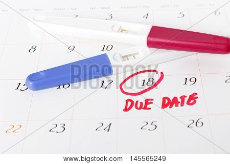 Pregnancy test with positive result lying on calendar background.circle due date 18th soft focus.
