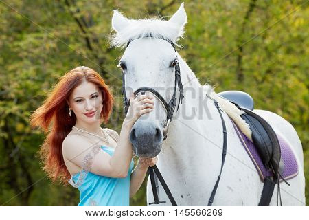 Young smiling red-haired woman holds white horse by bridle in park.