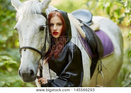 Young woman in black and white dress stands with horse in park.