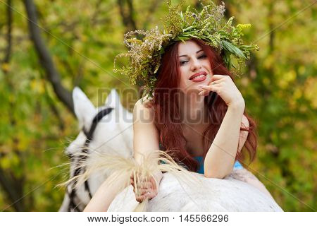 Young smiling red-haired woman with floral wreath on head lies on horseback in park.