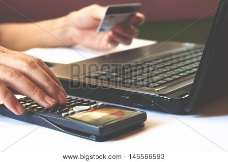 savings finances economy and office concept calculate how much cost or spending have with credit cards. Low light can be used for e-commerce laptop business technology and internet concept soft focus.