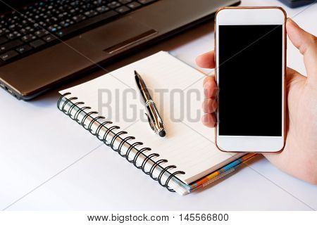Close up of a men using smart phone with blank mobile and calculator pen notebook. Smart phone with blank screen with clipping path. Hand using a white smart phone on a desk at home soft focus.