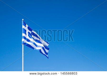 Flag Of Greece Waving On Flagpole Over Blue Sky