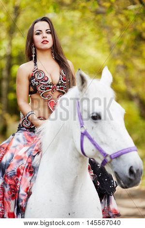 Young woman dressed in colourful dress decorated with playing cards  rides on horseback in park.