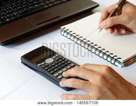 savings finances economytechnology and home concept close up of hands with calculator counting and taking notes to notebook and laptop on white table soft focus.