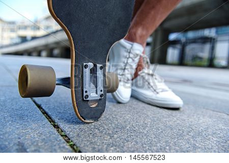 Close up of male legs near skateboard. Man is standing on road. Focus on skate