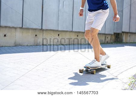 Young man is skating fast outdoors. He is standing on board and posing with balance