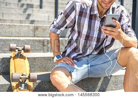 Happy young man is using smartphone and smiling. He is wearing earphones. Guy is sitting on steps near skate