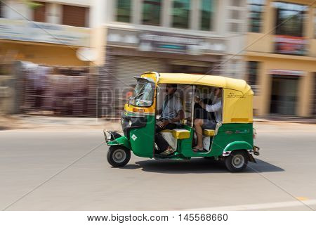 AGRA INDIA - 26TH MARCH 2016: A Tuk Tuk Rickshaw movong along a road in Agra during the day. People can be seen.