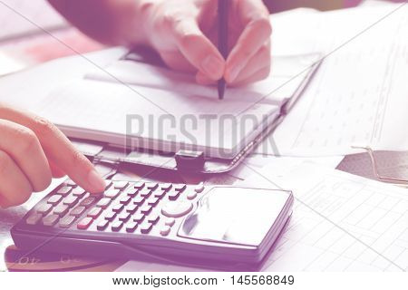 savings finances economy and home concept - close up of man with calculator counting making notes at home hand is writes in a notebook with books soft focus.