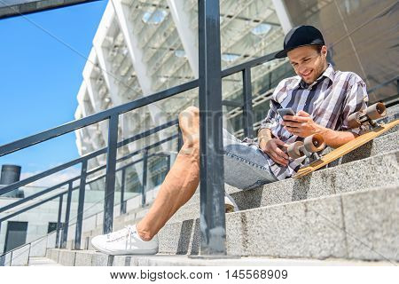 Cheerful young man is messaging on smartphone and smiling. He is sitting on stairs near his skate outdoors