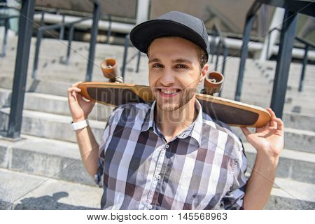 Happy male skateboarder is sitting on stairs and carrying skate on his shoulders. He is looking at camera and smiling