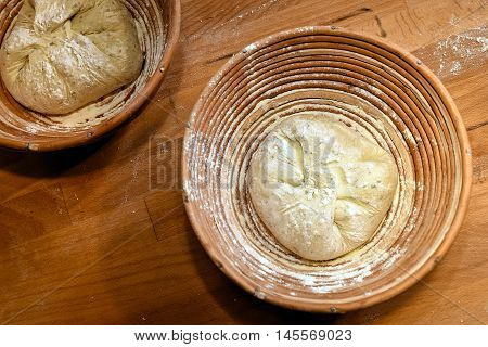 Making dough on wooden table background. dough in a wooden round bowl