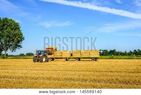 With the coupled pack charger the tractor driver charges loads the collected straw bales on the flat agricultural vehicles.