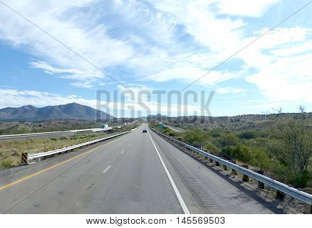 Long, straight highway through the Mojave Desert in Arizona, United States of America, two-lane roadway with marking and emergency lane, mountainous landscape and blue sky with clouds,