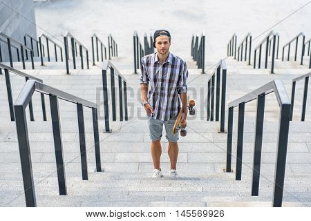 Cheerful male skateboarder is standing on steps and relaxing. He is holding skate and looking at camera with joy