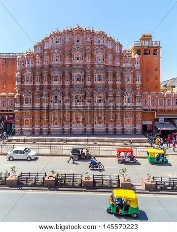 JAIPUR INDIA - 22ND MARCH 2016: The front of the Hawa Mahal (Palace of the Winds) in central Jaipur. Tuk Tuks other traffic and people can be seen outside on the street.