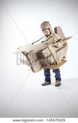 Young aviator in a homemade cardboard aircraft on gray background.