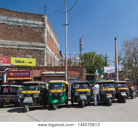 JAIPUR INDIA - 22ND MARCH 2016: Tuk Tuk Rickshaws parked in central Jaipur during the day. People can be seen.