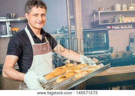 baker concept. Happy baker showing tray of fresh bread in the kitchen of the bakery