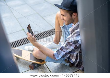 Carefree male skateboarder is making selfie on smartphone. He is looking at screen and smiling. Man is sitting on flooring near skate