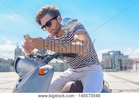 Cheerful young man is messaging on mobile phone with interest. He is sitting on scooter in city