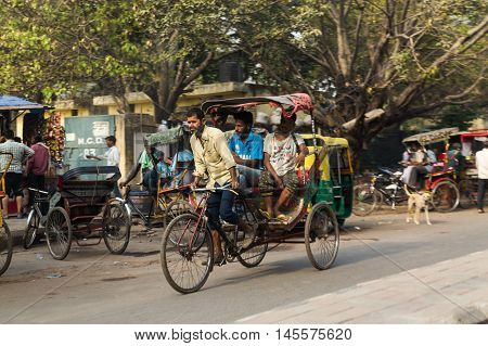 DELHI INDIA - 19TH MARCH 2016: Manual Tuk Tuks rickshaws drivers in Delhi India during the day. People can be seen.