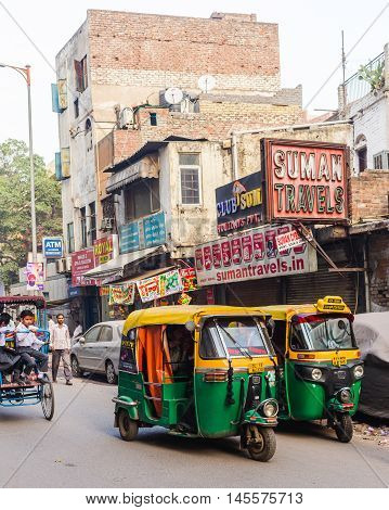 DELHI INDIA - 19TH MARCH 2016: A view of roads and streets in Delhi during the day showing Tuk Tuks rickshaws buildings and people.