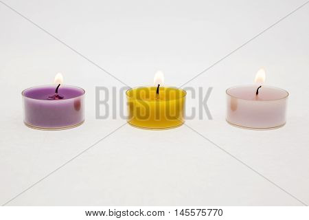 different colors of tea light candles with white background