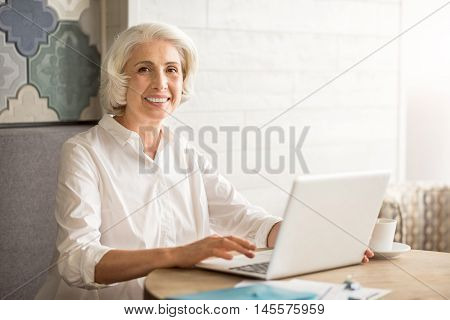 Never late to learn. Positive delighted senior woman sitting at the table and using laptop while expressing gladness