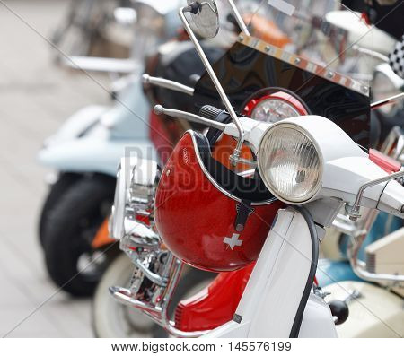 STOCKHOLM SWEDEN - SEPTEMBER 03 2016: Red shining retro helmet hanging on the handlebar of a vespa scooter before the start of the Mods vs Rockers event at the Saint Eriks bridge Stockholm Sweden September 03 2016