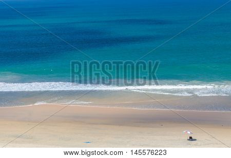 Beach and sea background in South India. An umbrella and deck chair can be seen. There is space for text.