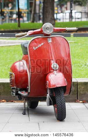 STOCKHOLM SWEDEN - SEPTEMBER 03 2016: Red retro vespa scooter parked in the park before the start of the Mods vs Rockers event at the Saint Eriks bridge Stockholm Sweden September 03 2016