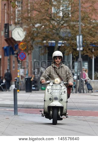 STOCKHOLM SWEDEN - SEPTEMBER 03 2016: Mods man driving a white retro vespa scooter the city in background in the Mods vs Rockers event at the Saint Eriks bridge Stockholm Sweden September 03 2016