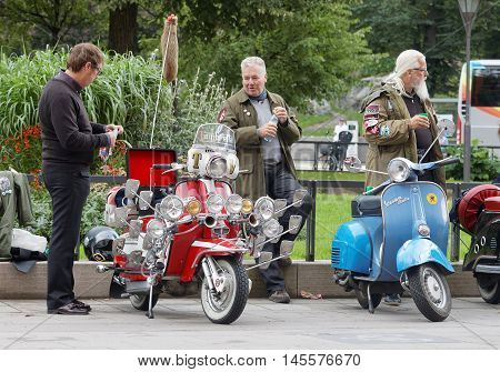 STOCKHOLM SWEDEN - SEPTEMBER 03 2016: Older men dressed as mods posing at their retro vespa scooters before the start of the Mods vs Rockers event at the Saint Eriks bridge Stockholm Sweden September 03 2016