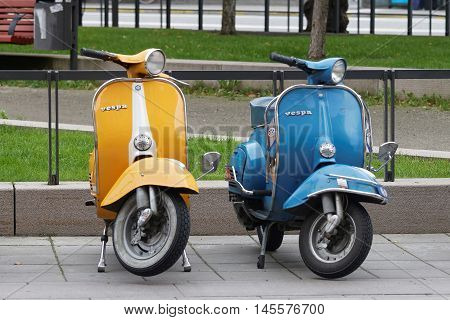 STOCKHOLM SWEDEN - SEPTEMBER 03 2016: One yellow and one blue retro vespa scooters parked before the start of the Mods vs Rockers event at the Saint Eriks bridge Stockholm Sweden September 03 2016