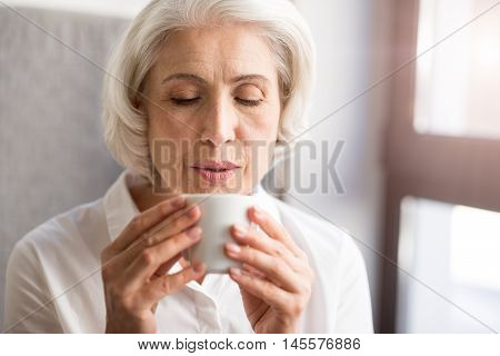 Nice taste. Pleasant delighted woman holding cup and drinking tea while resting in the cafe