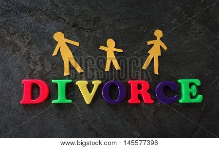 Divorce play letters with paper family on dark background