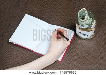 Glass jar with retirement fund full of money and female hand writing in notebook