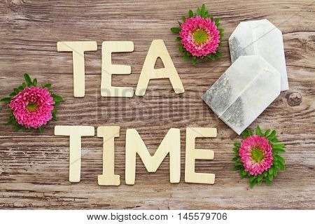 Tea time written with wooden letters, tea bags and pink daisies