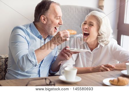 Happy meal. Overjoyed delighted senior couple sitting at the table and eating croissants and sitting at the table while resting in the cafe