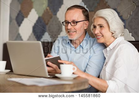 Modernize your outlook. Cheerful delighted senior couple sitting at the table and smiling while suing laptop