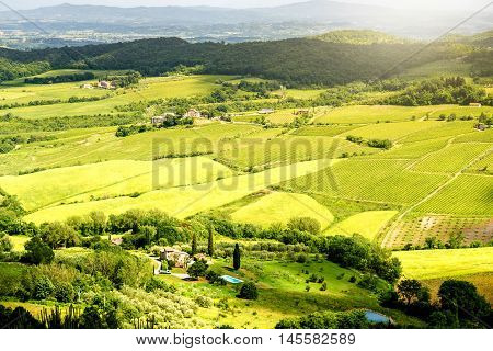 Beautiful tuscan landscape view on the green meadow with farmlands near Montepulciano town in Italy