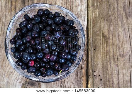 Bilberry in Crystal Bowl on Rustic Wooden Background